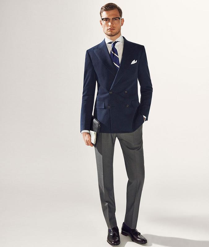 Парень в темно-синем пиджаке и серых брюках
