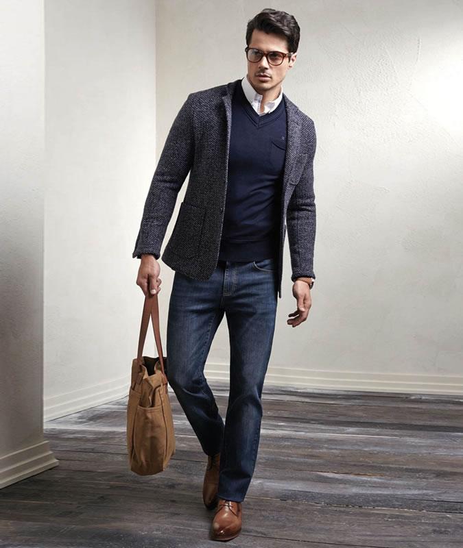 Парень в сером свободном пиджаке и темно синих джинсах
