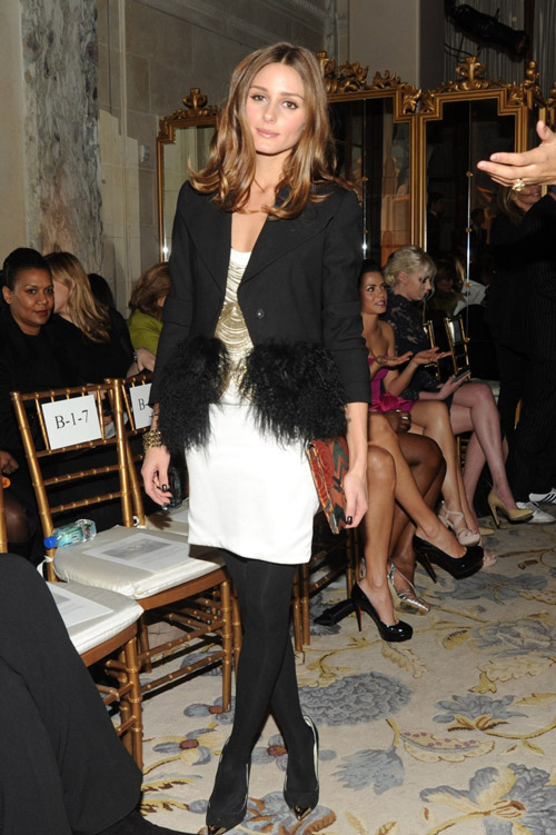 На показе Marchesa во время Недели моды В Нью-Йорке в черном блейзере и белой юбке