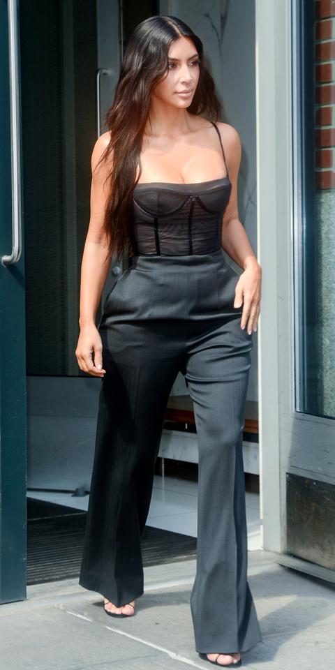 Ким Кардашян в черных брюках и топе бюстье