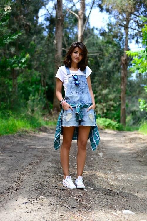 Девушка в белой футболке, джинсовый комбинезон и сникерсы