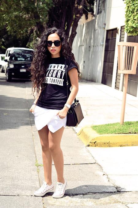 Девушка в белых шортах, черная футболка и кеды
