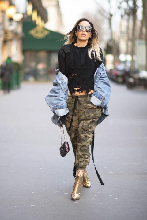 Девушка в брюках милитари, черный джемпер, джинсовая куртка и золотые боильоны