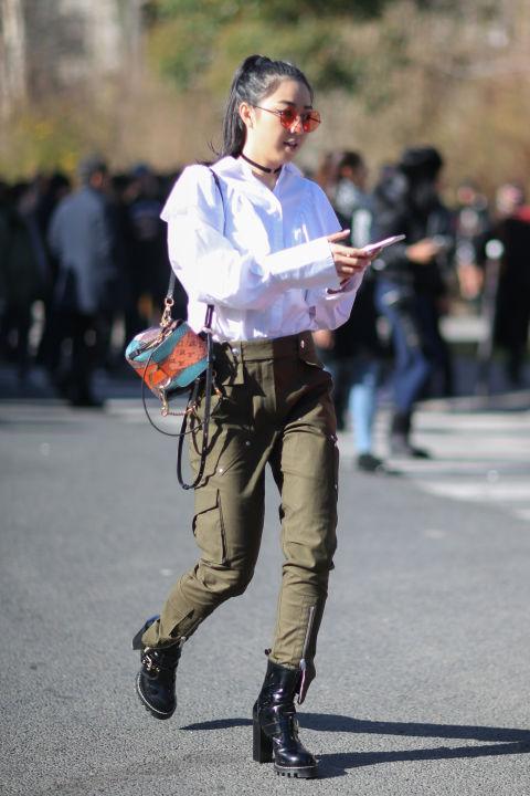 Девушка в брюках милитари с накладными карманами, белая блузка, черные ботинкм