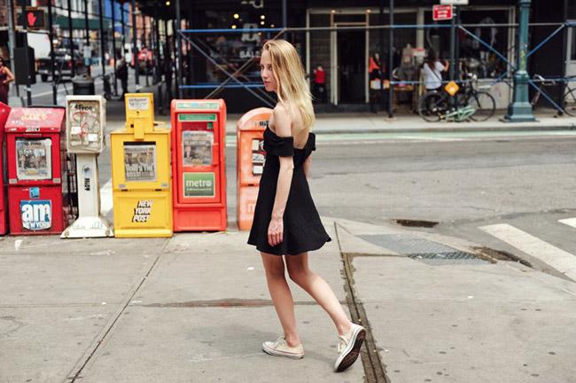 Девушка в чернм мини платье с открытыми плечами и белых сникерсах