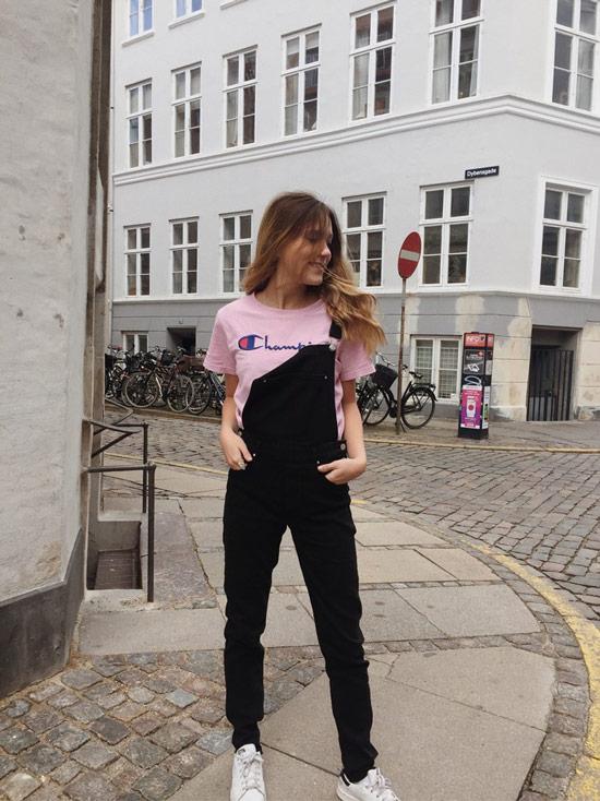 Девушка в черном комбинезоне и розовой футболке с надписью