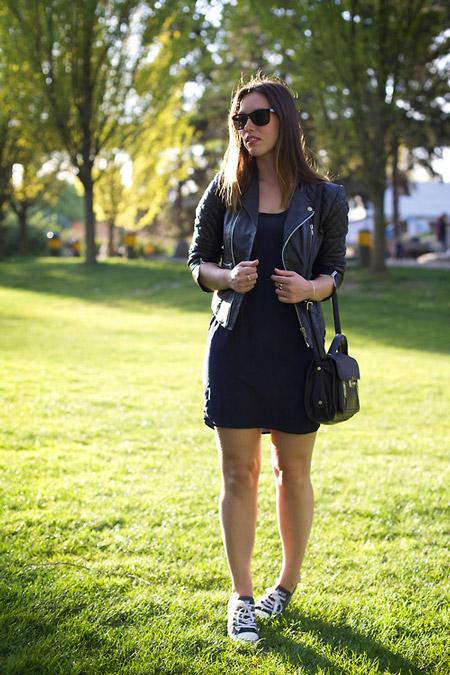 Девушка в черном мини платье, косуха и черная сумк и кеды