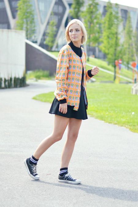 Девушка в черном мини платье, оранжевый бомбер с принтом и кеды конверсы