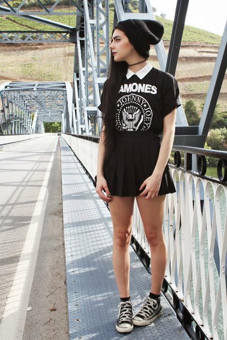 Девушка в черной мини юбке, футболка с принтом, шапка и кеды