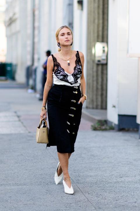 Девушка в черной юбке миди и белом топе с кружевами