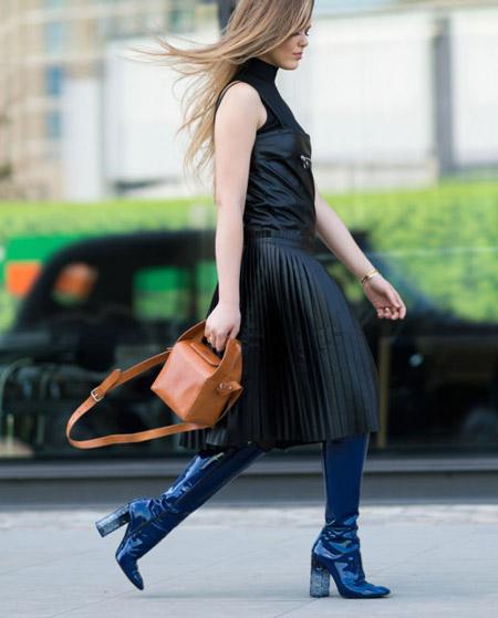 Девушка в черной юбке миди, топ и синие сапоги