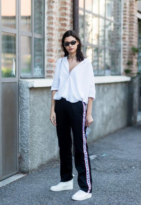 Девушка в черных брюках с лампасами, белая блузка и кеды