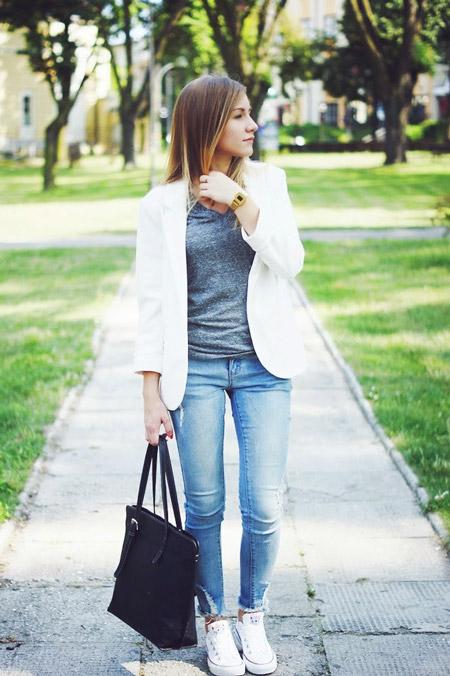 Девушка в джинсах, серая футболка, пиджак и белые сникерсы