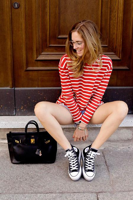 Девушка в джинсовых шортах, бело-еоасный свитшот и черные кеды