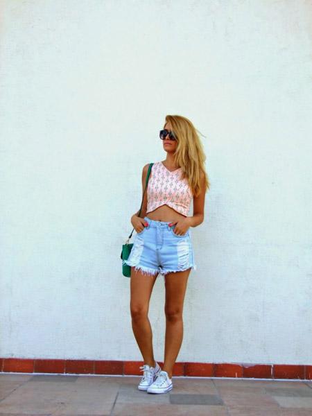 Девушка в голубых шортах, розовый кроп топ и кеды