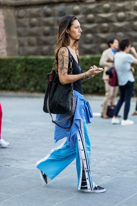 Девушка в голубых штанах, черный топ и большая сумка