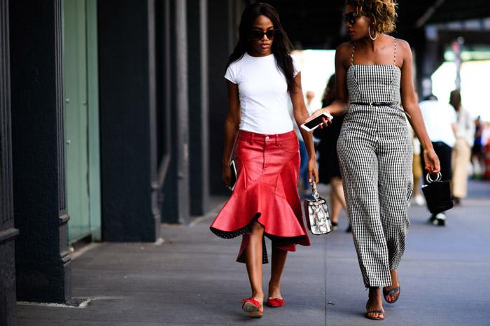 Девушка в красной кожаной юбке миди и белой футболке