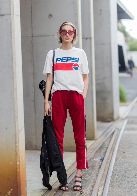 Девушка в красных брюках и футболка с надписью, черные босоножки и бомбер