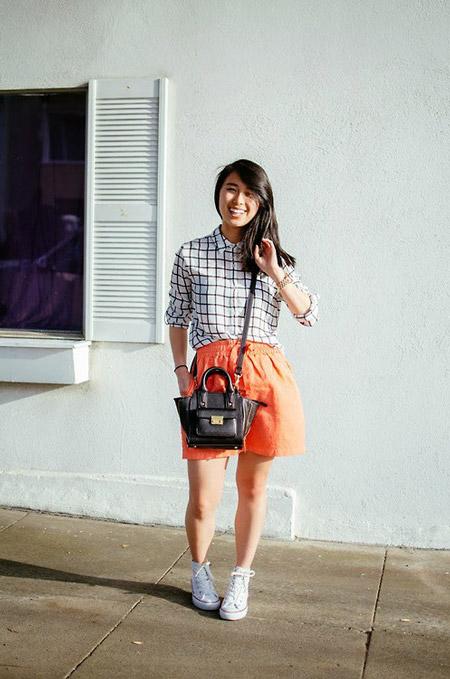 Девушка в оранжевой юбке, белая рубашка в клетку и кеды