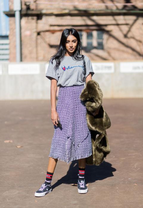 Девушка в пестрой юбке миди, серая футболка и кеды