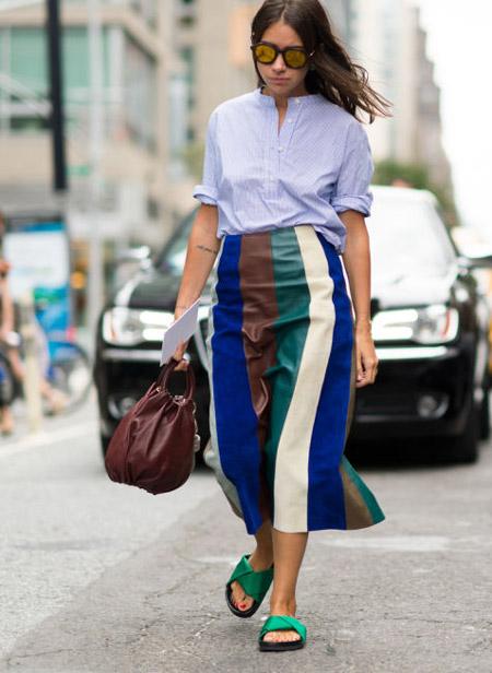 Девушка в полосатой юбке миди и голубой рубашке