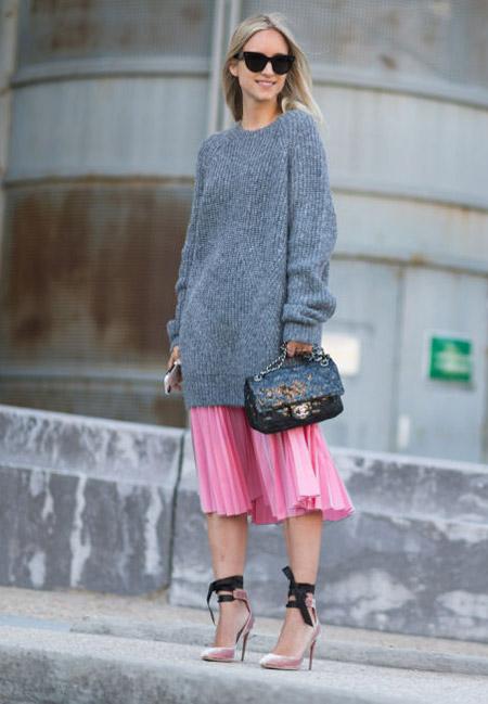 Девушка в розовой плиссированной бке миди и сером свитере оверсайз
