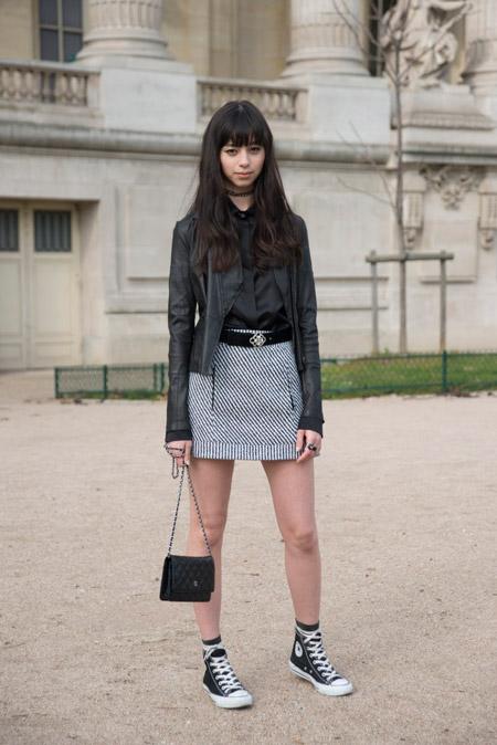 Девушка в серой мини юбке. черная куртка и конверсы с белыми шнурками