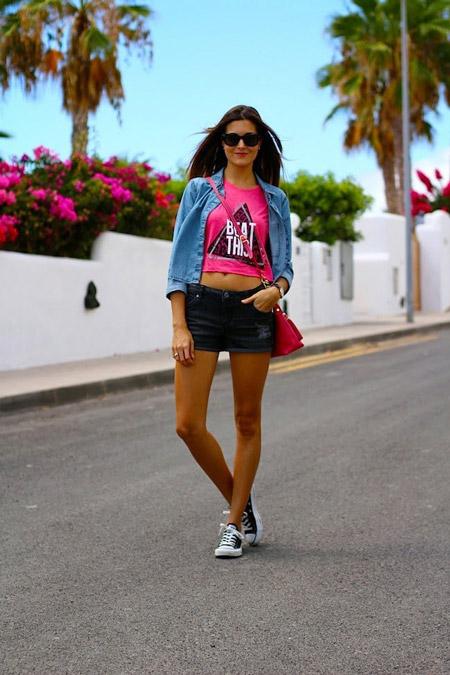 Девушка в шортах, укороченная майка, джинсовка и черные сникерсы