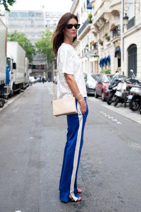 Девушка в синих брюках в стиле спорт шик и белой блузке