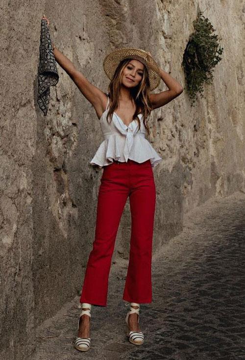 Модный блогер в красных брюках, топе и соломенной шляпе sincerelyjules