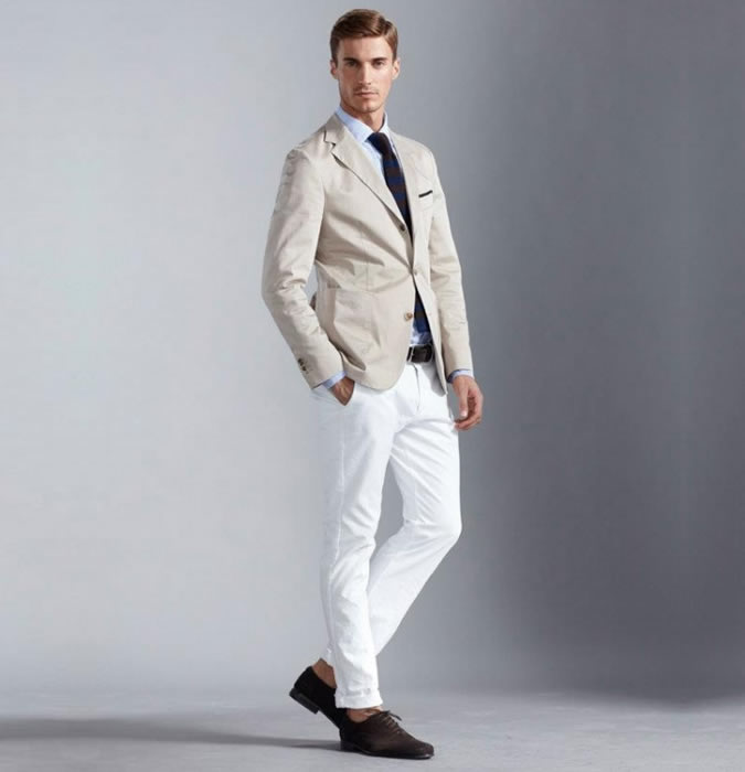 Мужчина в белых джинсах, сером блейзере и коричневых ботинках