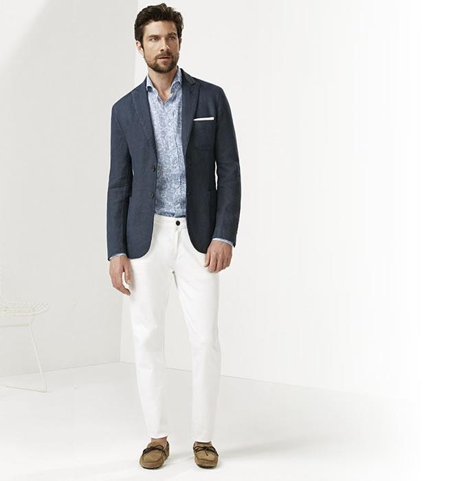 Мужчина в белых джинсах, синем блейзере, рубашке с принтом и лоферах
