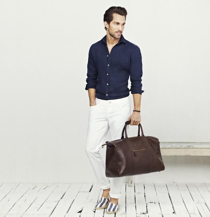 Мужчина в белых джинсах, синей рубашке и полосатых лоферах