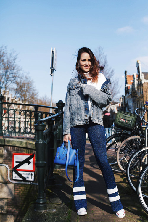 Блогер в белом свитере, джинсовке и синих штанах с космическим принтом