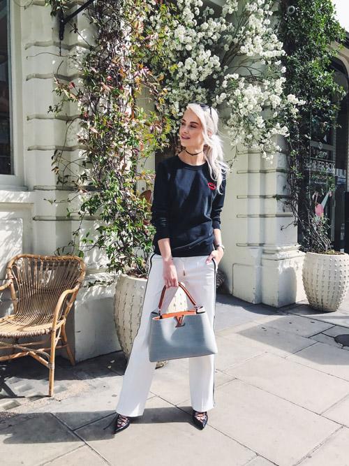 Блогер в белых спортивных брюках и темно-синем джемпере