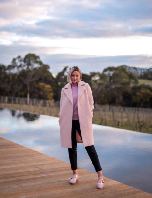 Блогер в черных брюках и нежно-розовом пальто