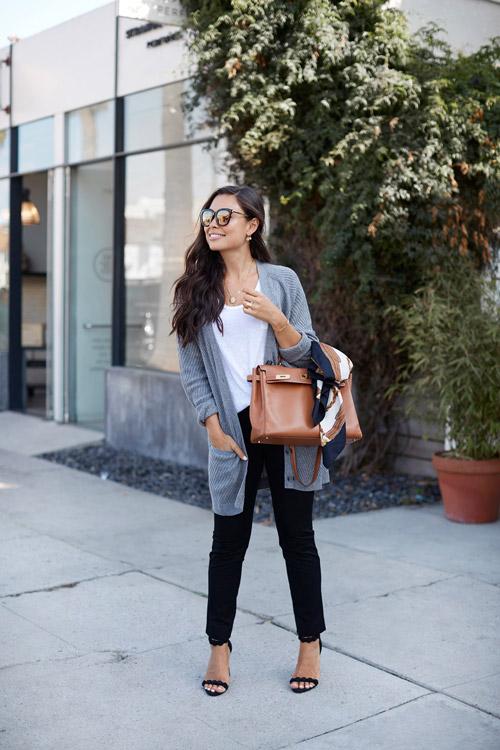 Блогер в черных джинсах, белом топе и сером кардигане
