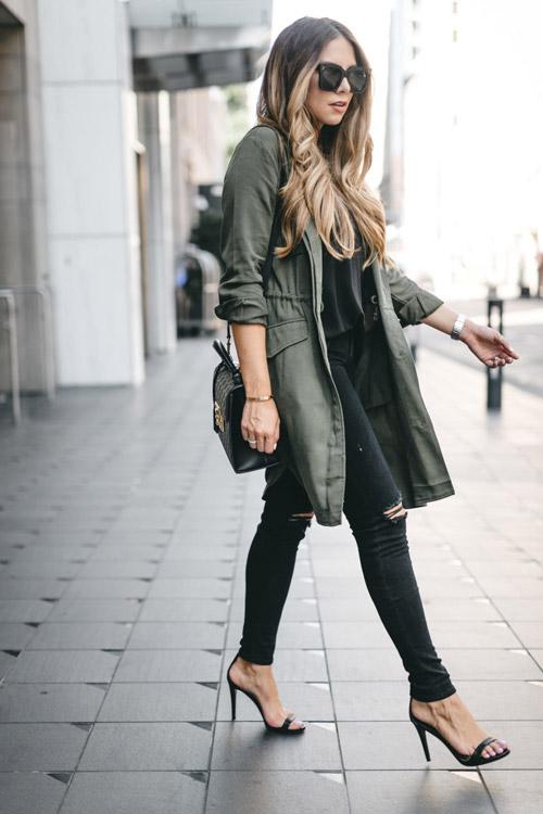 Блогер в черных рваных джинсах, футболке и парке цвета хаки