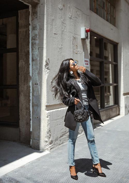 Блогер в джинсах, серой футболке и пиджаке от смокинга
