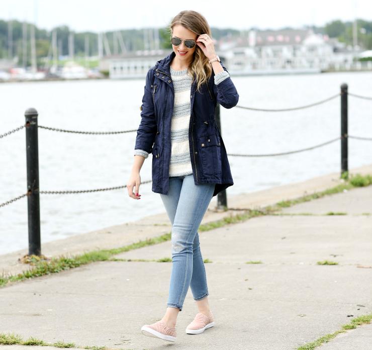Блогер в джинсах скинни, полосатом джемпере и темно-синей куртке