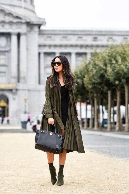 Блогер в плиссированном плаще цвета хаки, лодочках и маленьком черном платье