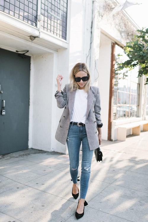 Блогер в потертых джинсах, белой футболке, сером пиджаке и черных лодочках