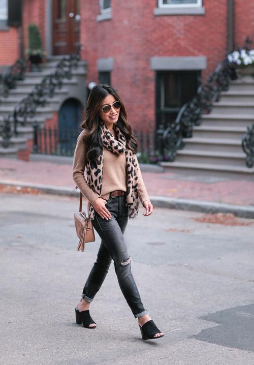 Блогер в серых рваных джинсах, джемпере и с шарфом хомутом на шее