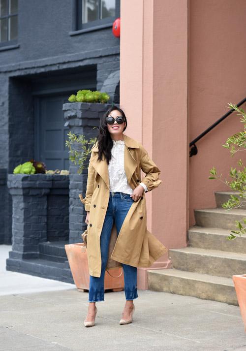 Блогер в синих джинсах, блюзе с рюшами и плаще