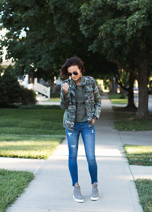 Блогер в синих джинсах, темно-зеленой футболке и армейской куртке