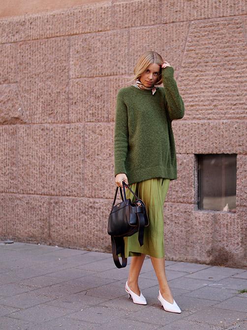 Блогер в зеленой свободной юбке, джемпере и с шарфиком на шее