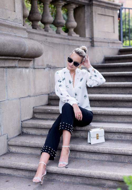 Девушка в белой блузе и синих укороченных брюках.