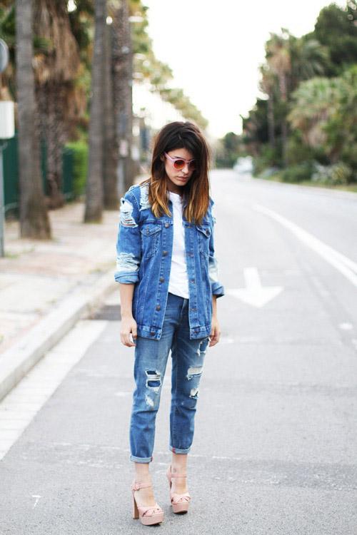 Девушка в белой футболке и рваных синих джинсах и джинсовке