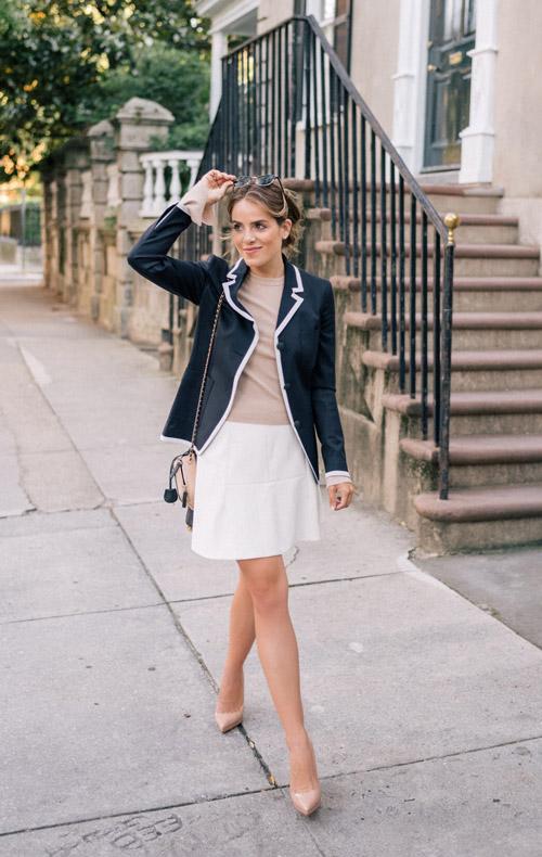 Девушка в белой мини юбке и черном жакете.