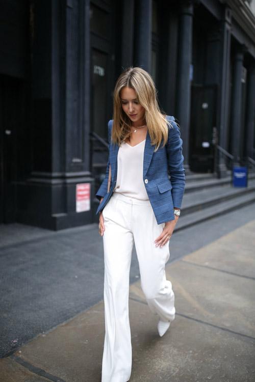 Девушка в белых брюках, топе и синем жакете.